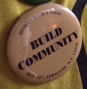 "Picture of button Steve Taylor created for the Center on Human Policy, now being used by students at the SU protests and sit-in. Ivory/tan color button with ""Build Community"" in capital letters, and the ""Human Policy Press"" and a very dated address around the edge."